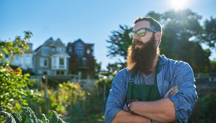 proud gardener with beard looking at his crops in urban communal garden
